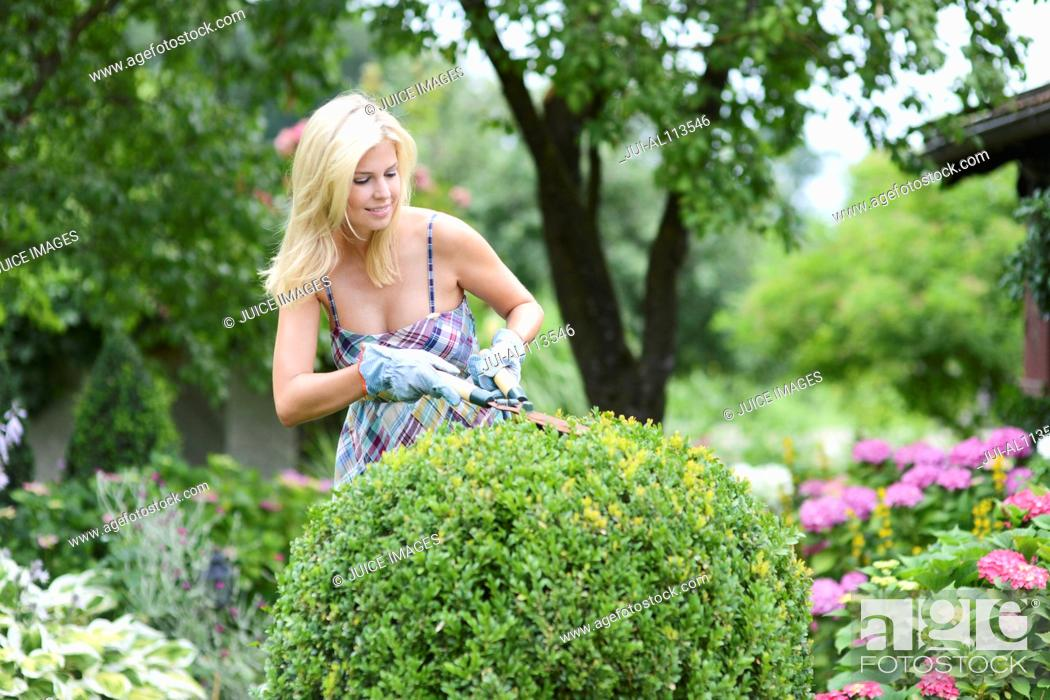 Stock Photo: Mid adult woman, in garden, smiling.