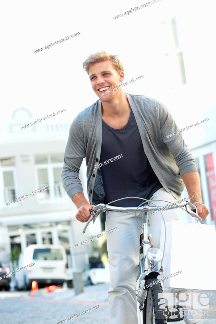Stock Photo: Smiling young man cycling.