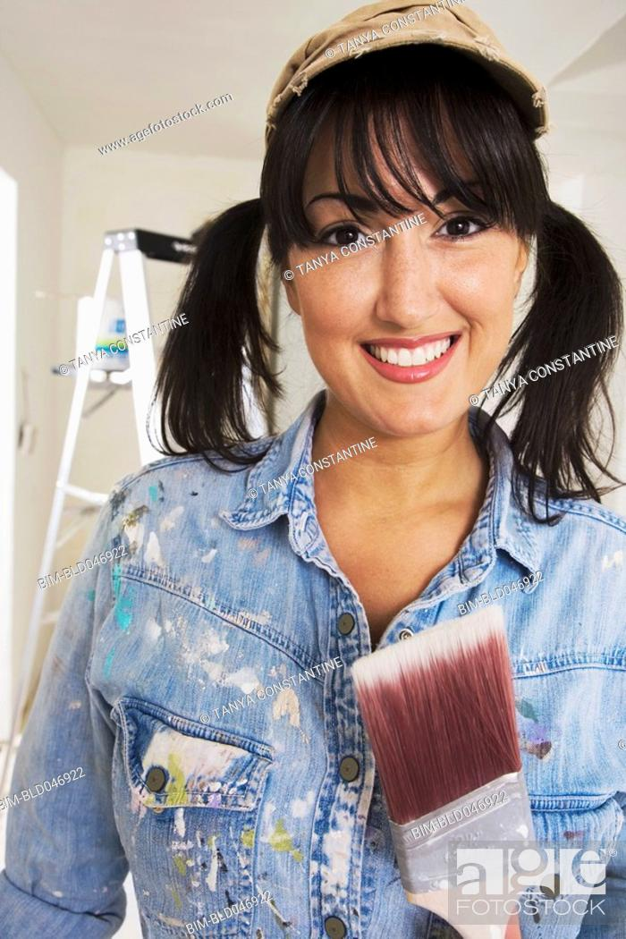 Stock Photo: Middle Eastern woman holding paint brush.