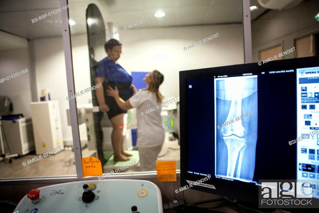 Stock Photo: Reportage in a radiology centre in Haute-Savoie, France. A technician carries out a knee x-ray on a patient with the beginnings of osteoarthritis.