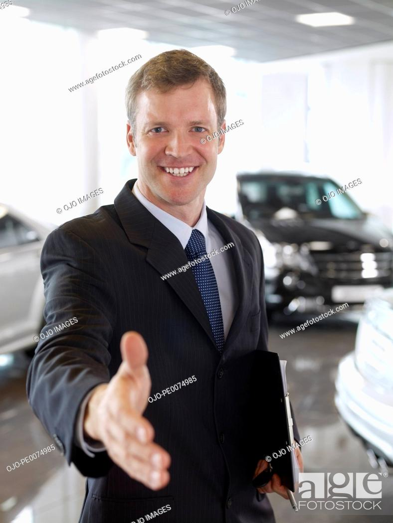 Stock Photo: Greeting salesman in automobile showroom.