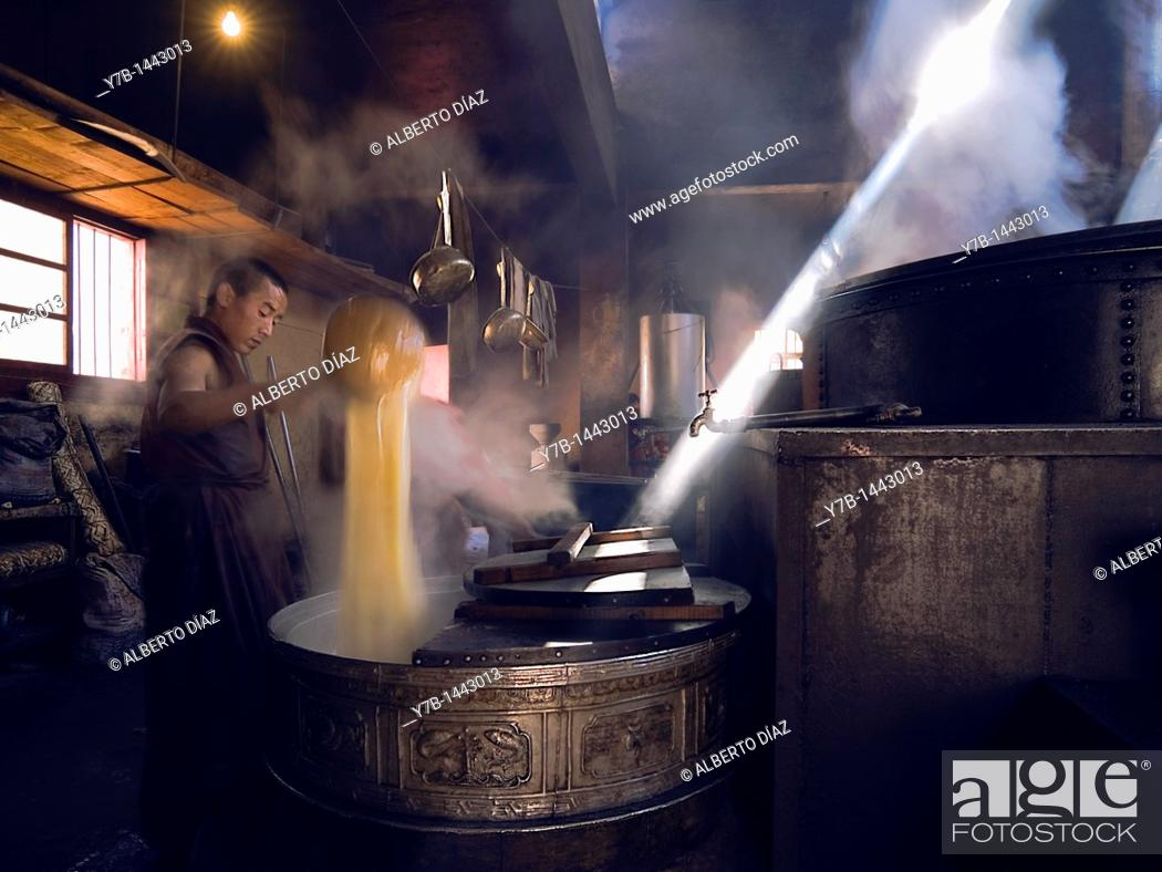 Stock Photo: Monk stirring the tea in the kitchen of Jampa Ling Monastery.
