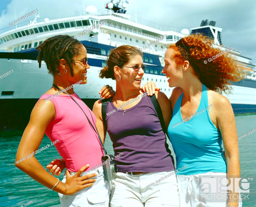 Stock Photo: Close-up of three young women standing on the beach in front of a cruise ship, Bermuda.