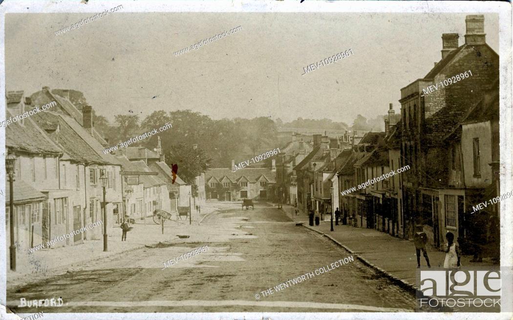 Stock Photo: The Village, Burford, Oxford, near Witney, Oxfordshire, England. Showing Shop/Premises of WM Harvey.