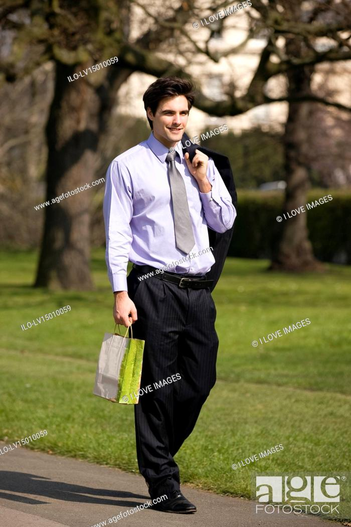Stock Photo: A businessman walking in a park, holding a carrier bag.