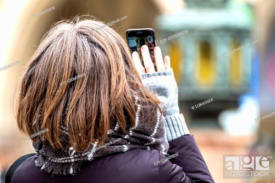 Stock Photo: Lady photographing with smart phone with life picture of the historic town hall of Munich, Germany - Europe.