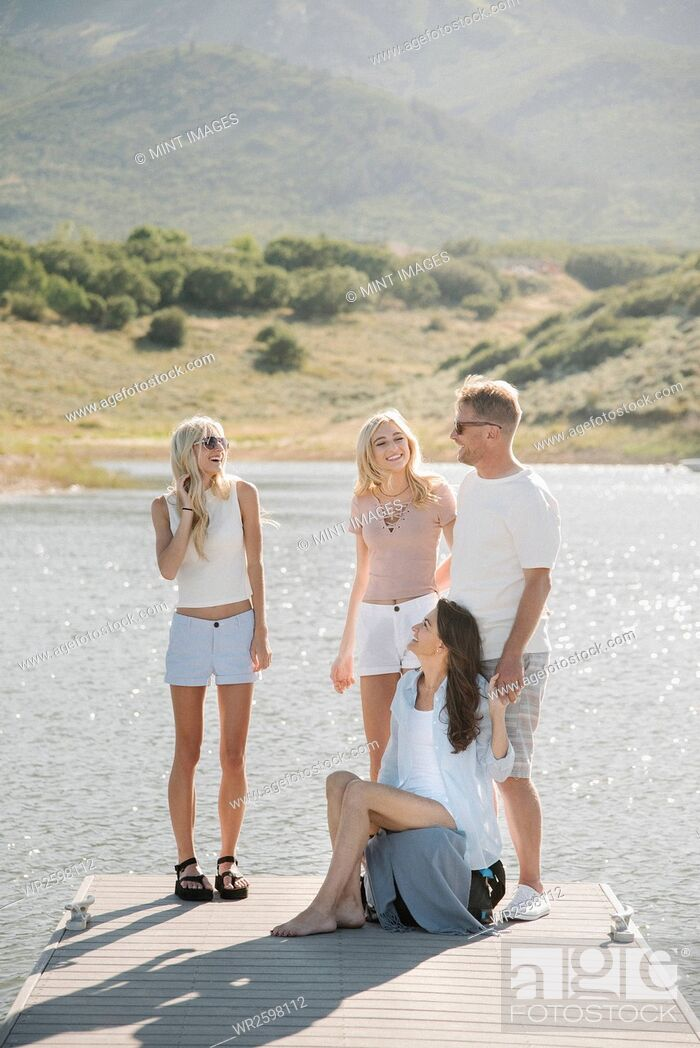 Imagen: Man, woman and their two blond daughters standing on a jetty.