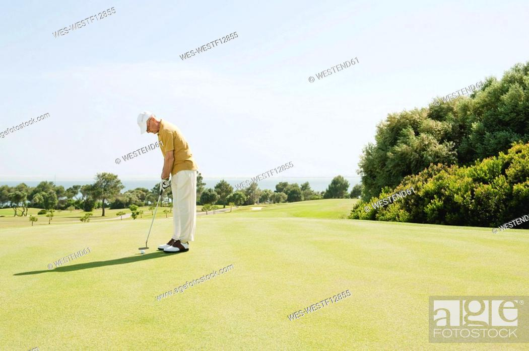 Stock Photo: Spain, Mallorca, Senior man playing golf, side view.