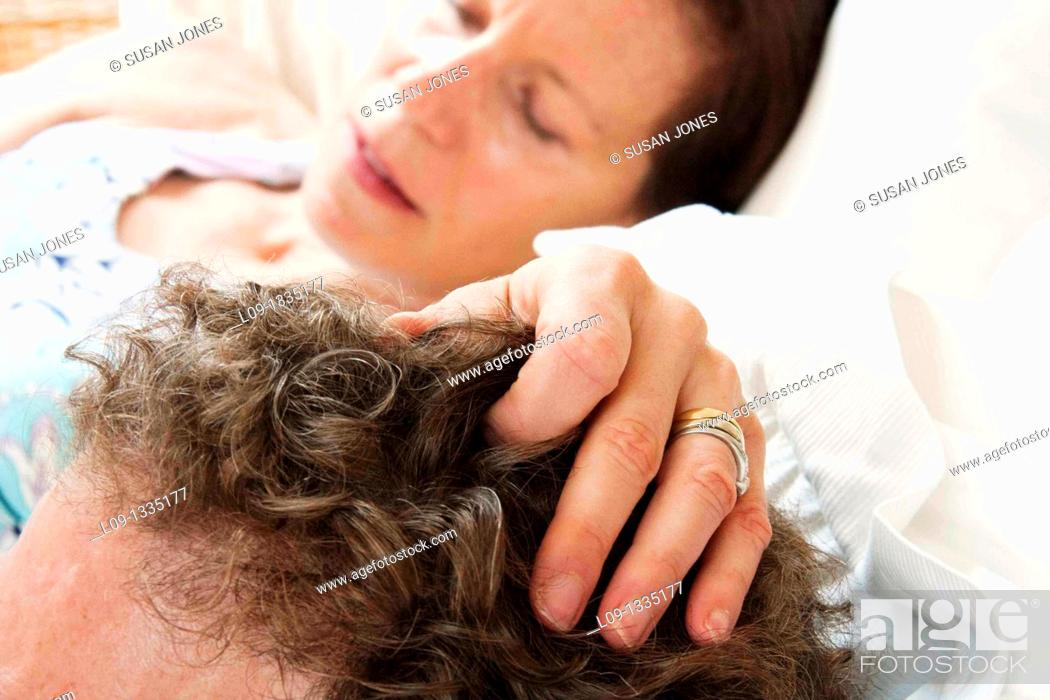 Stock Photo: Woman's hand on man's head.
