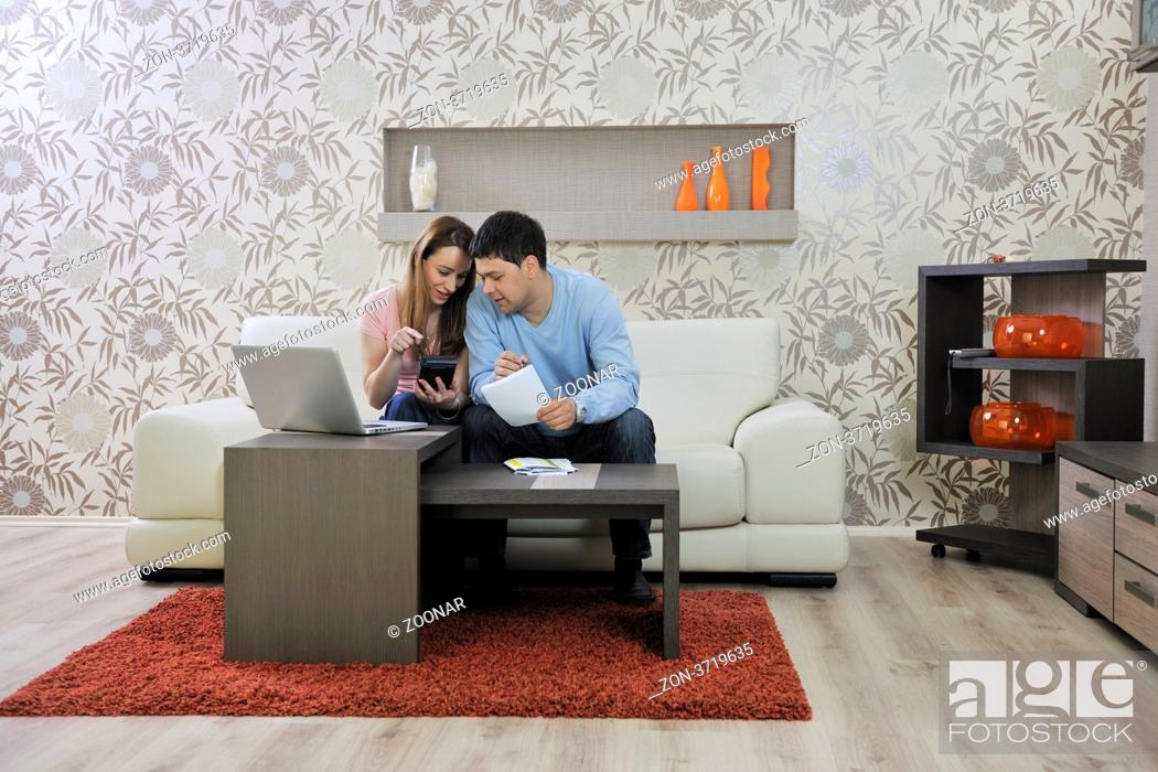 Stock Photo: young couple at home with modern livingroom indoor working on laptop on house finance and planing.