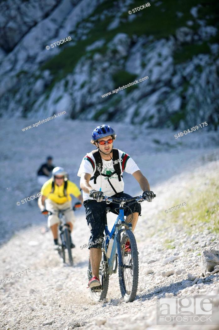 Stock Photo: Three young men on mountainbikes in a rocky landscape, selective focus.