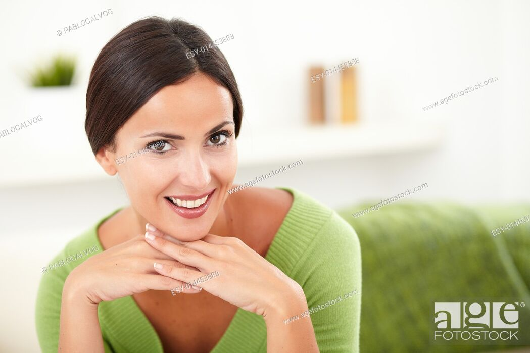Stock Photo: Beautiful woman in green shirt contemplating while looking at the camera - copy space.