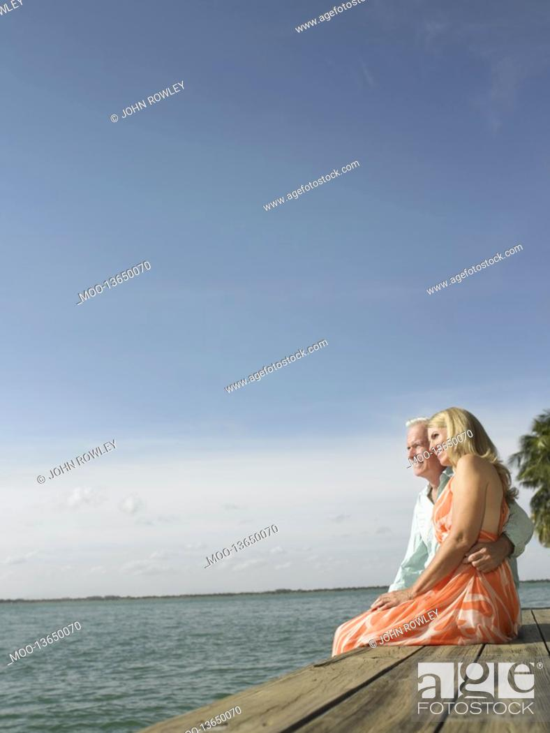 Stock Photo: Couple sitting on edge of pier side view.