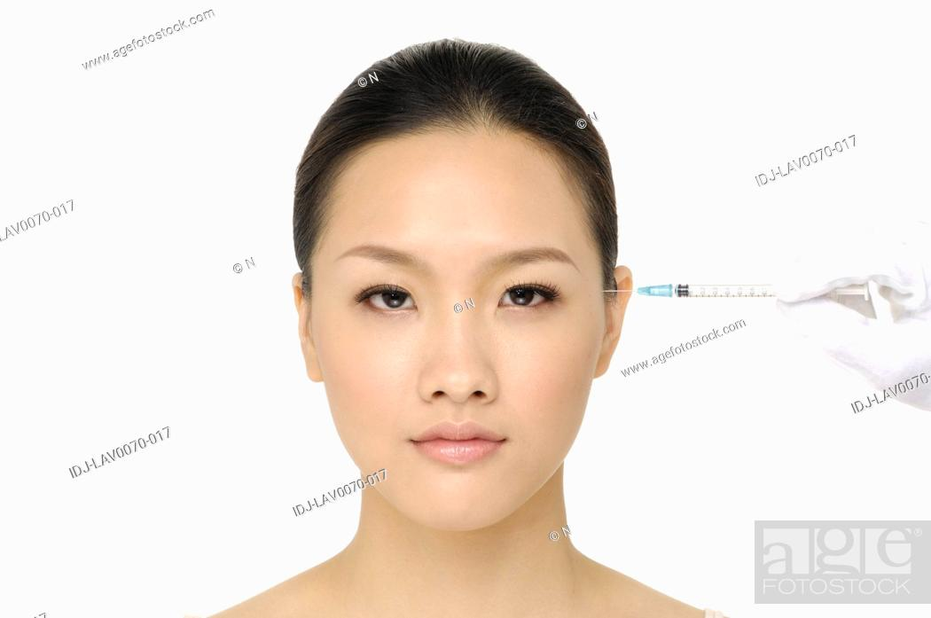 Stock Photo: injection of botox on female temple - female portrait.