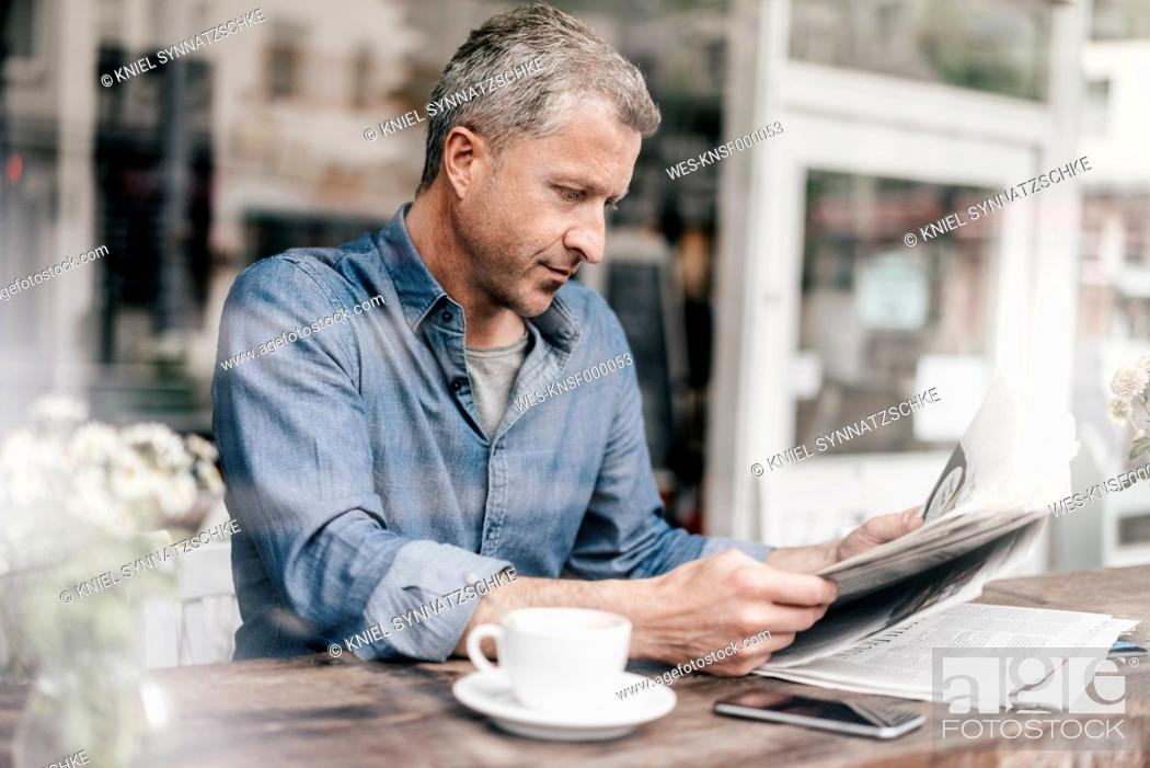 Stock Photo: Mature man sitting in cafe reading newspaper.