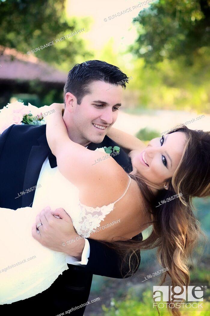 Imagen: smiling groom lifting happy bride after wedding.