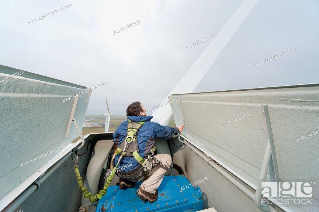 Imagen: Alaska native technican checking for blade damage atop a wind turbine, St. Paul Island, Southwestern Alaska, USA, Summer,.