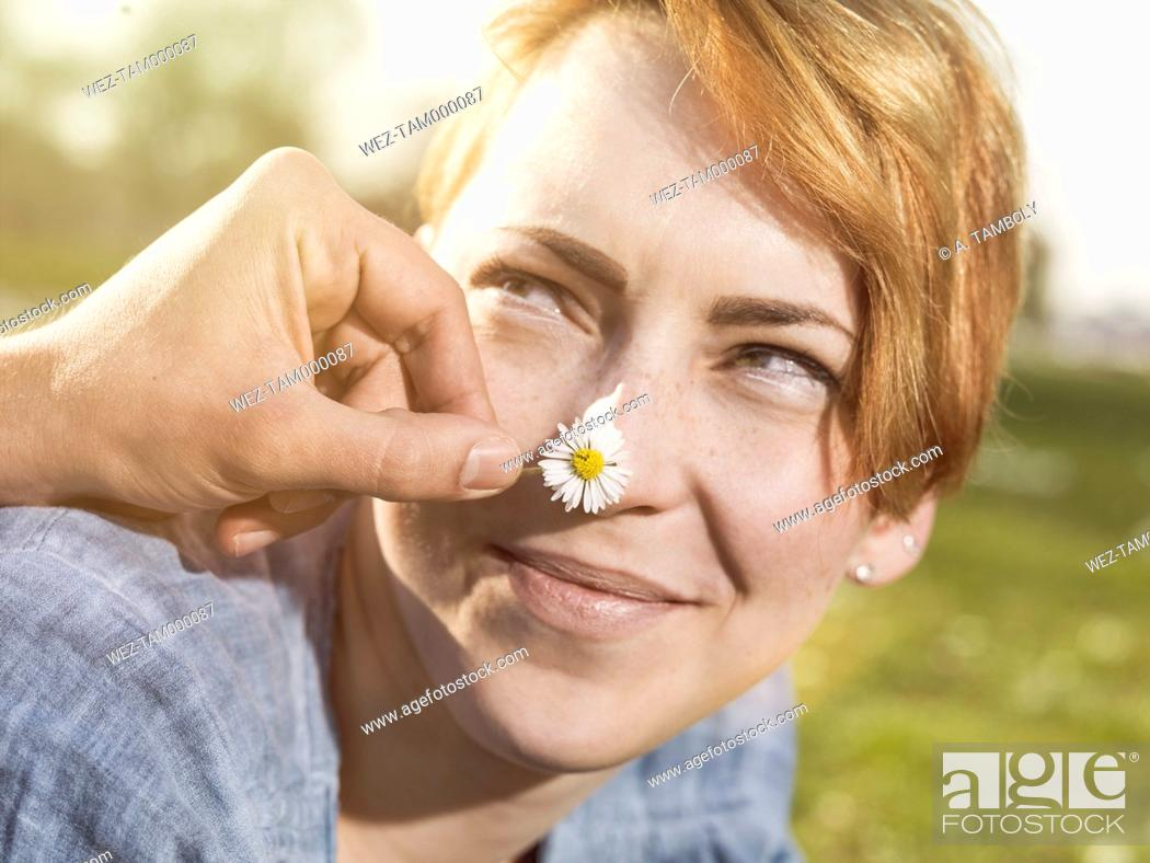 Stock Photo: Young man tickling his girlfriend with a daisy.
