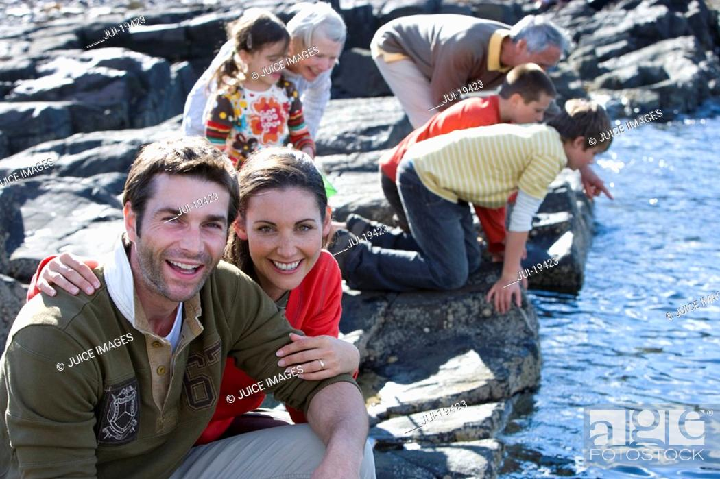 Stock Photo: Mid adult couple sitting on rock, family in background.