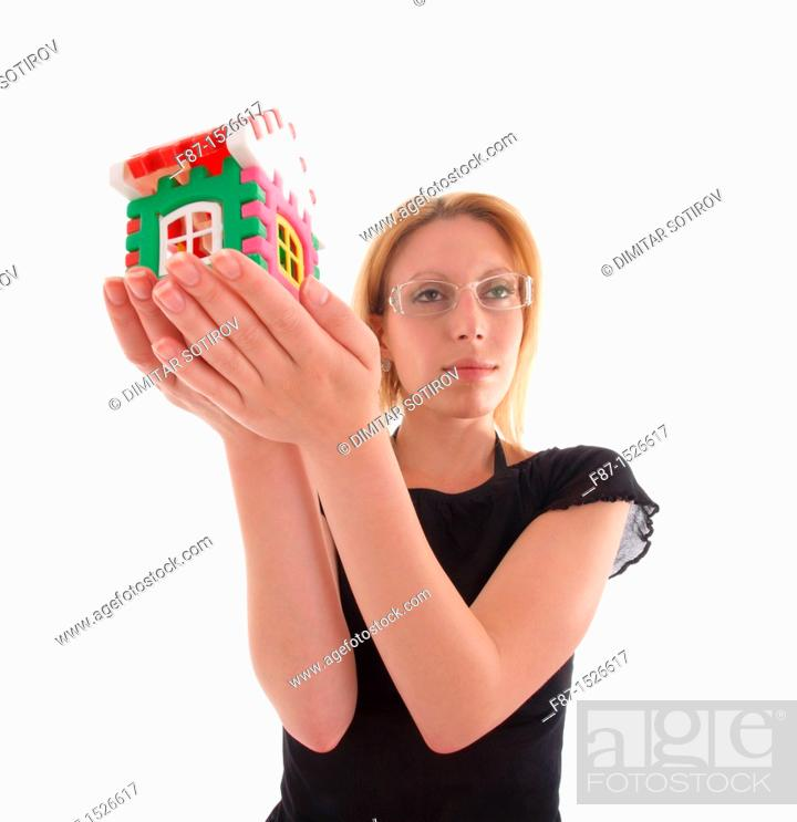 Stock Photo: Young woman with little house in hand isolated on white.