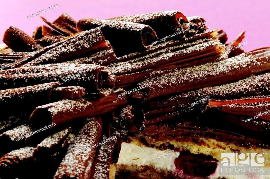 Stock Photo: Chocolate curls on chocolate cream cake with cherries.
