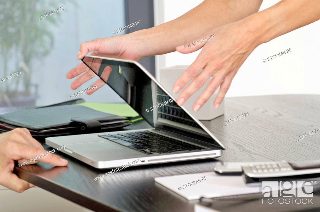 Stock Photo: Woman closing laptop at desk.