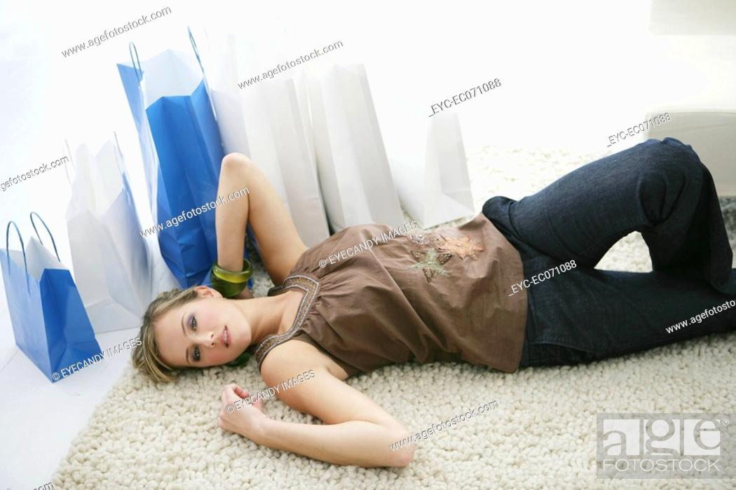 Stock Photo: Young woman relaxing on floor with shopping bags.