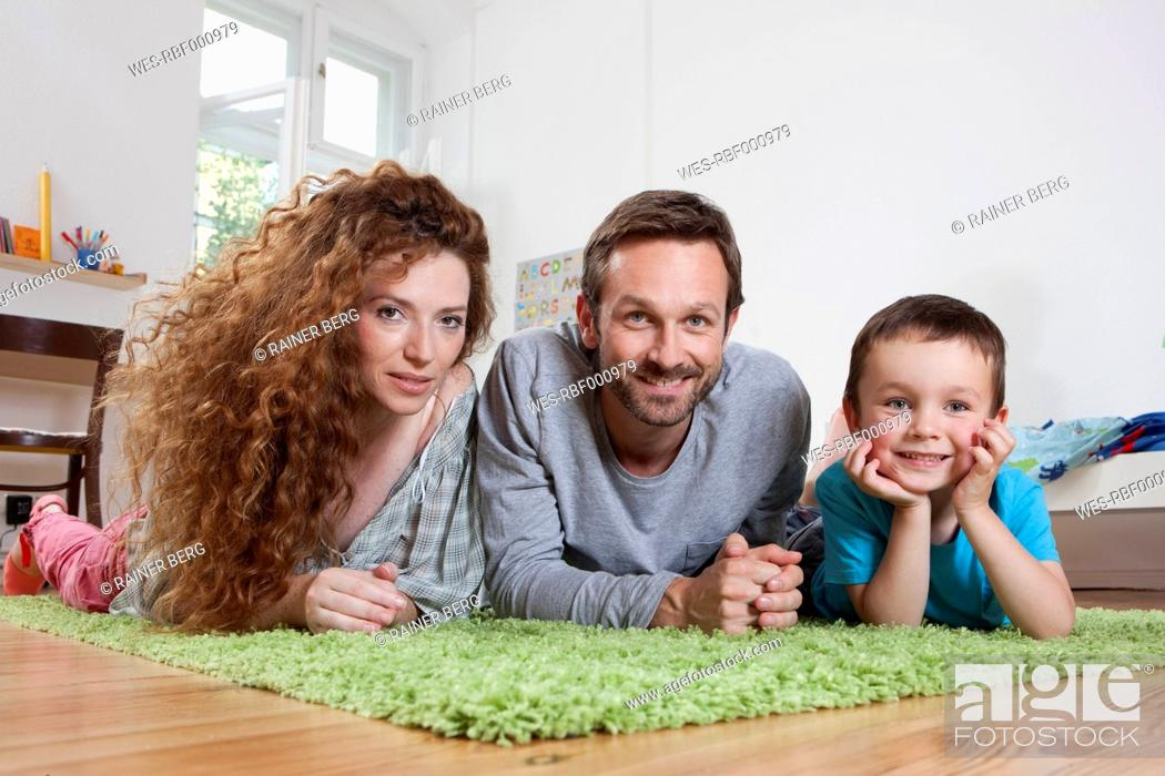 Stock Photo: Germany, Berlin, Family on floor, smiling, portrait.