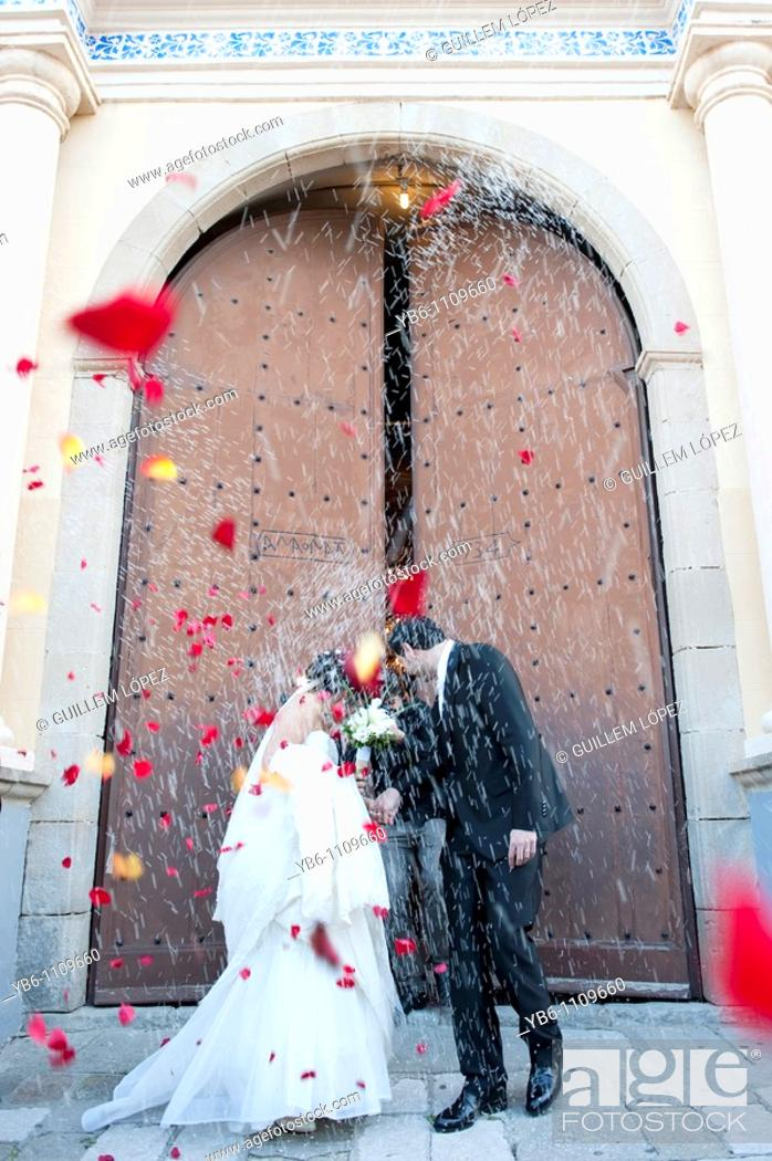 Stock Photo: A just married couple coming out of the church with people throwing rice and rose petals to them.