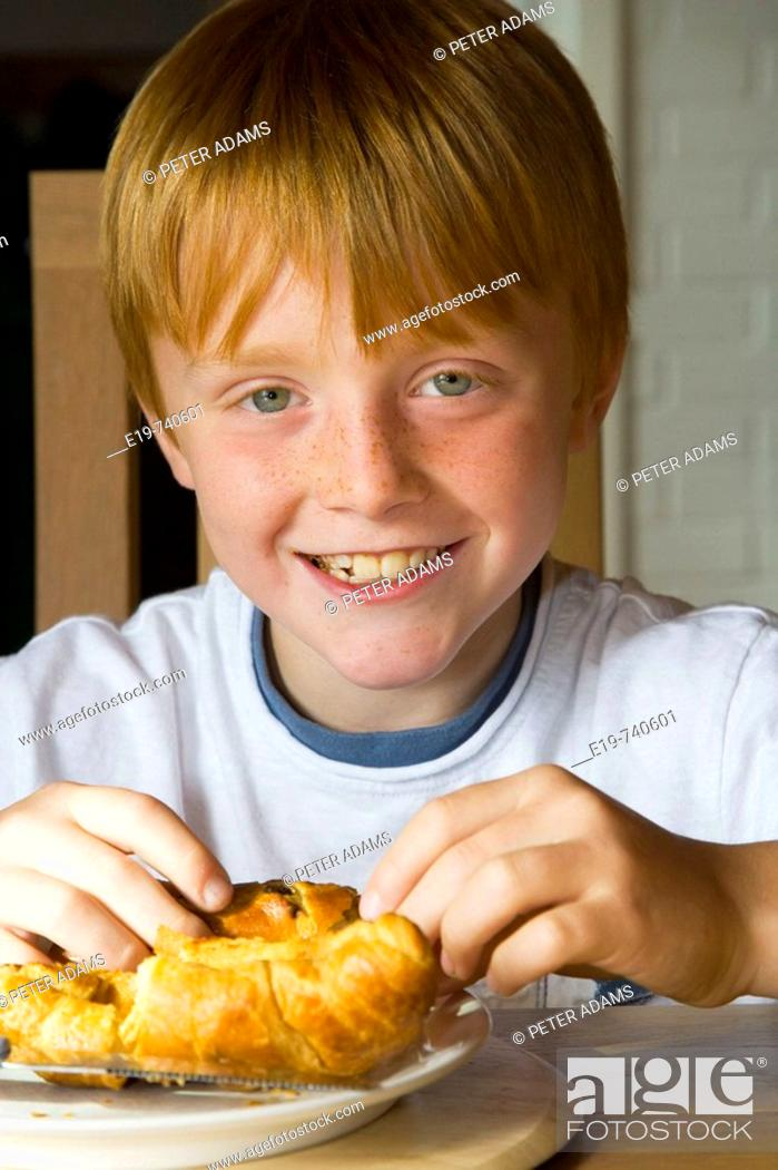 Stock Photo: 8 yr old boy eating croissants.
