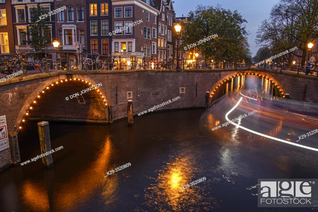 Stock Photo: Reflections of bridge lighting in canals at dusk, Amsterdam, North Holland, Netherlands.