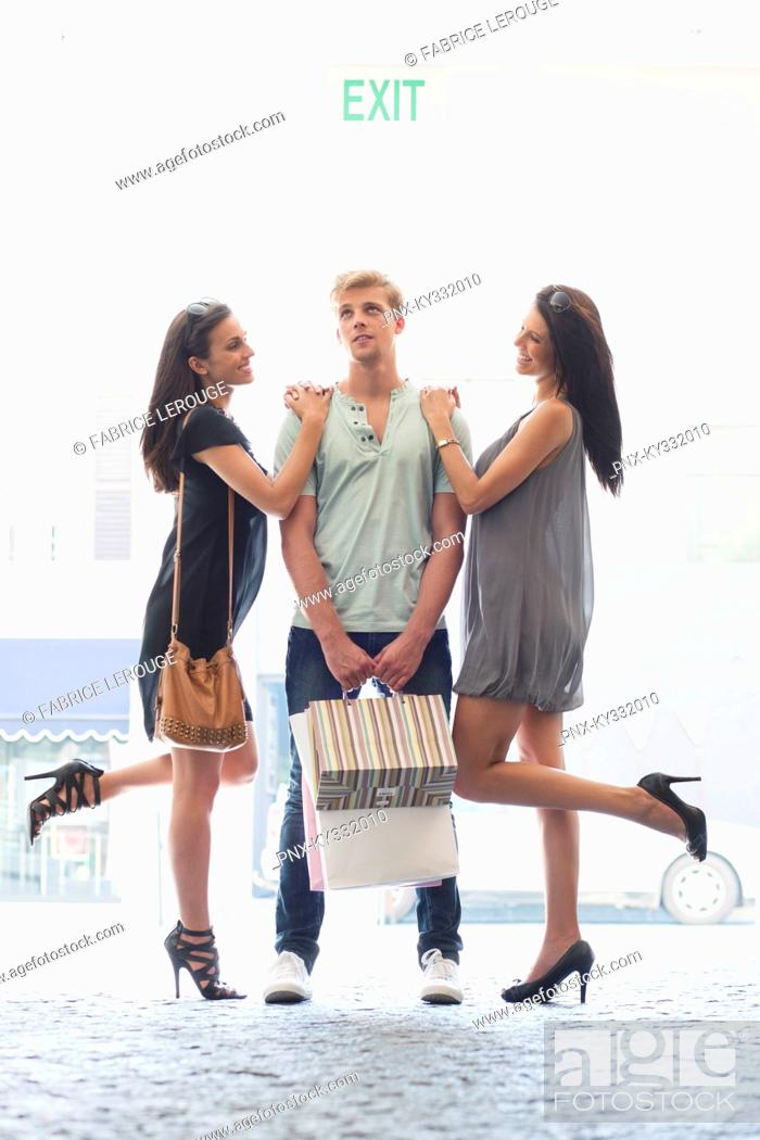 Stock Photo: Two young women standing with hands in man's shoulders.