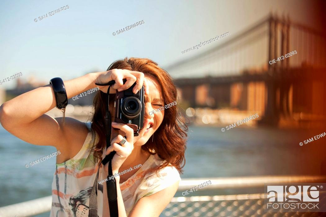 Stock Photo: Woman taking picture by city cityscape.