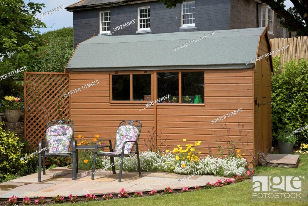 Stock Photo: Devon England Uk, Barn Style Garden Shed With A Small Patio And Chairs.