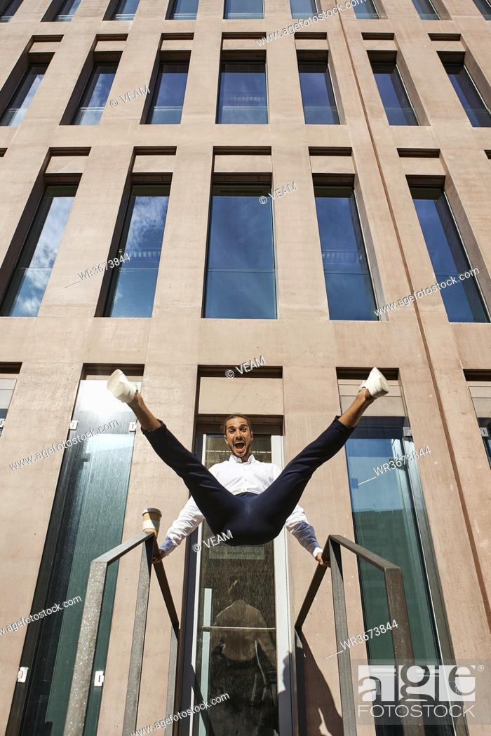 Stock Photo: Happy entrepreneur dancing against building.