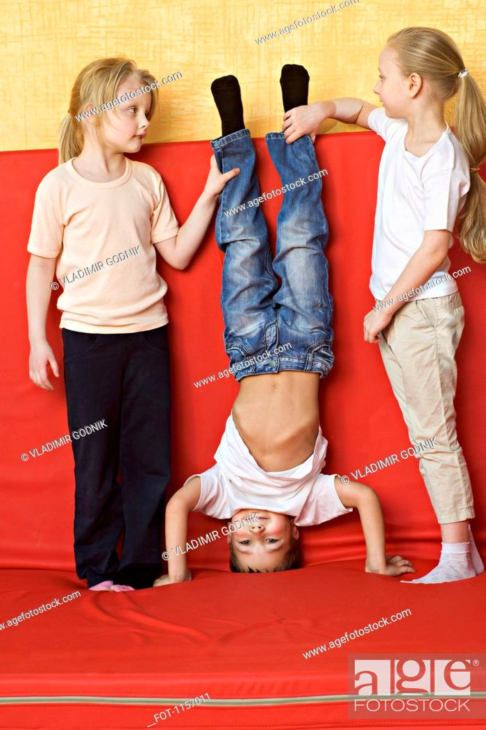 Stock Photo: Two girls holding a boy upside down.