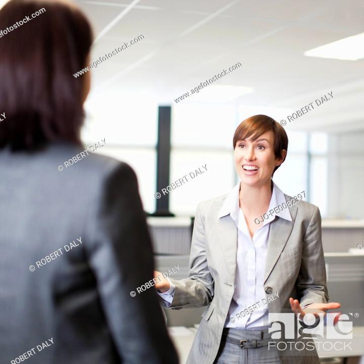 Stock Photo: Businesswoman gesturing and talking to co-workers.