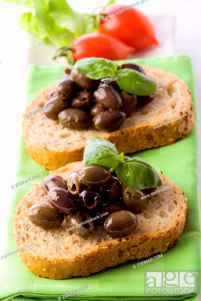 Stock Photo: photo of delicious sliced bread with olives and basil.
