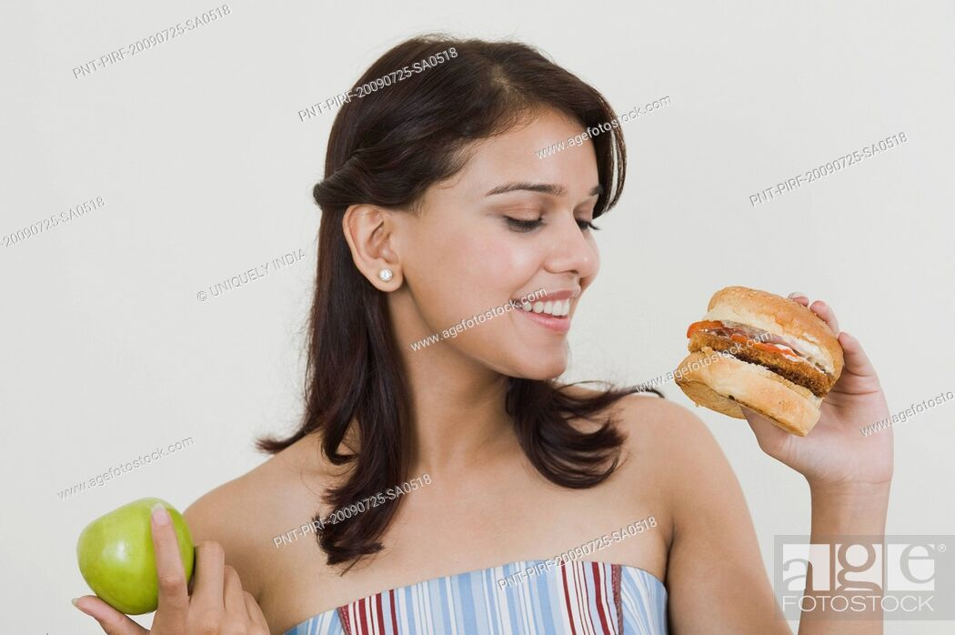 Imagen: Woman holding a burger and a green apple.
