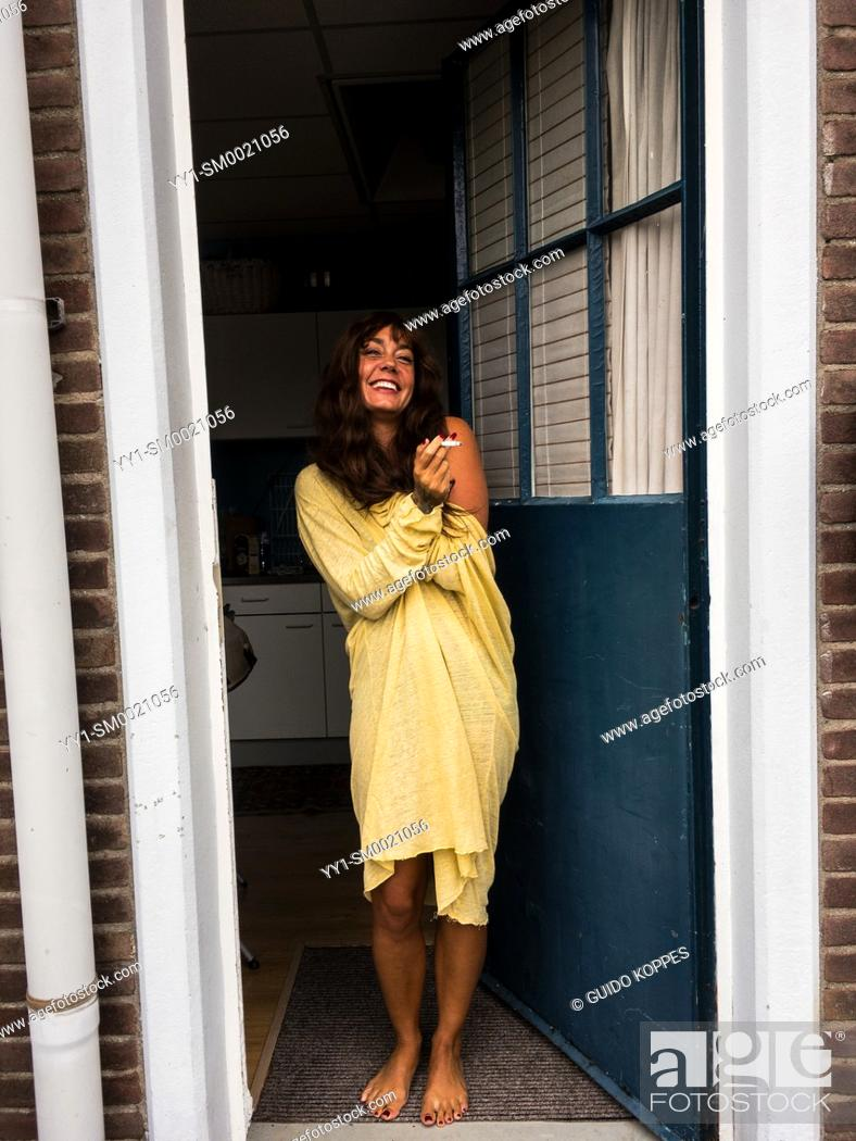 Stock Photo: Vucht, Netherlands. Adult, caucasian woman smoking her cigarette while standing on het front door step.