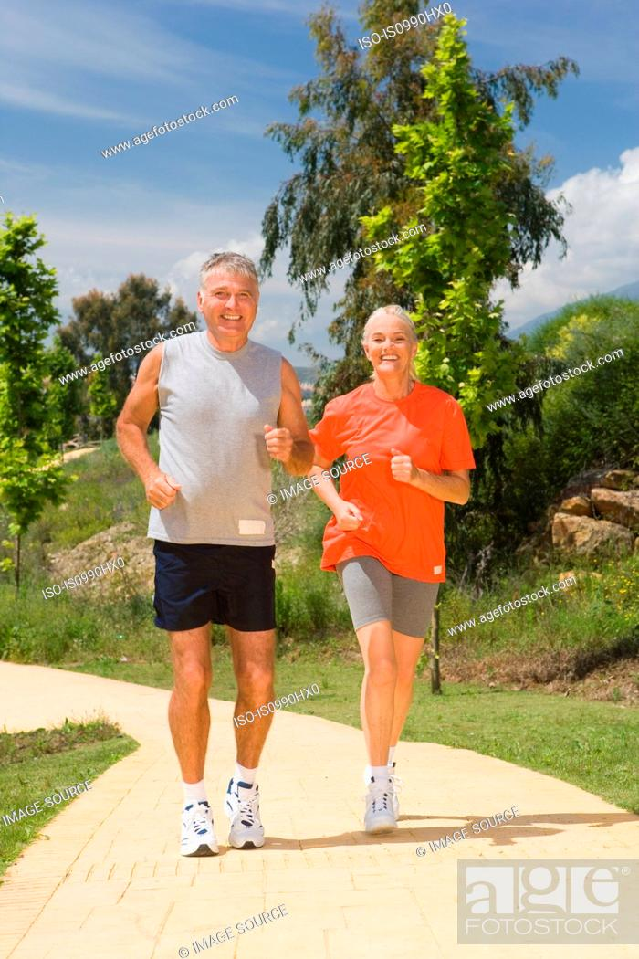 Stock Photo: Mature couple jogging together.