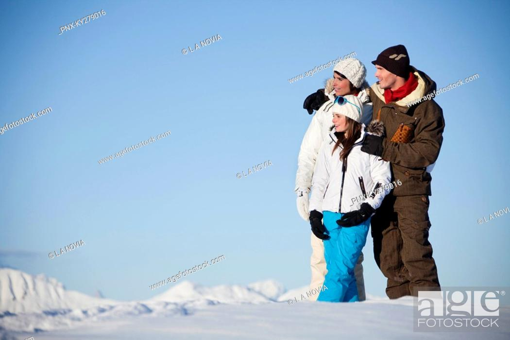 Stock Photo: Couple and daughter in ski wear looking away.