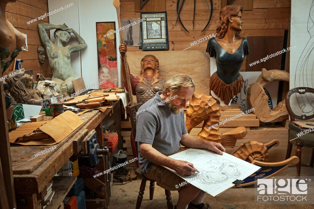 Imagen: A craftsman, woodworker seated on a stool in a workshop working on a drawing, sketching using charcoal. Surrounded by wooden carved and painted female ship's.