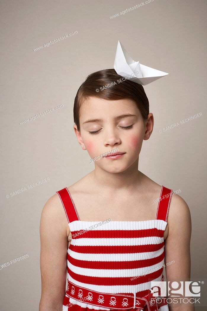 Stock Photo: Portrait of little girl with paper boat on her head.