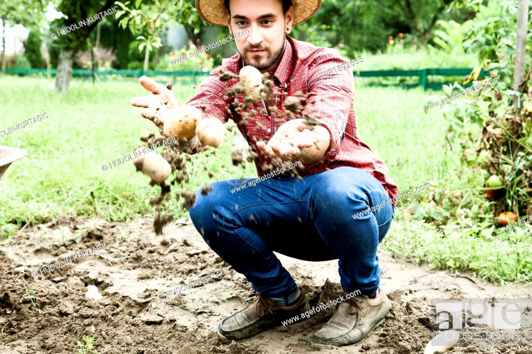 Stock Photo: Young man throwing up raw potatoes.