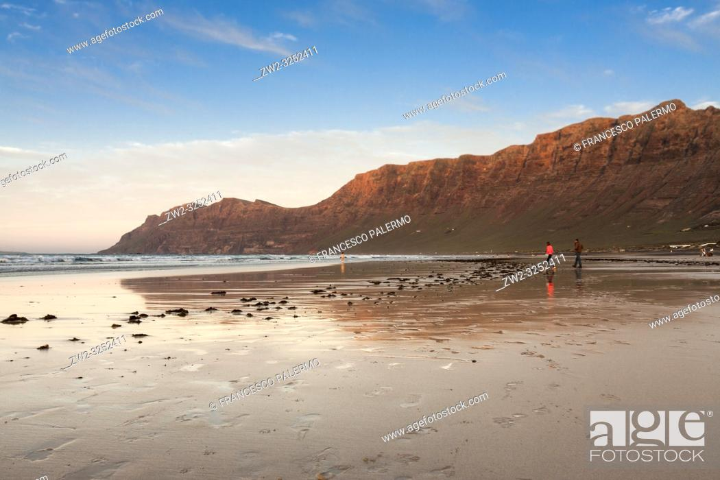 Stock Photo: Sunset in the shore of a beach with persons walking along the shore of the sea. Famara, Lanzarote. Spain.
