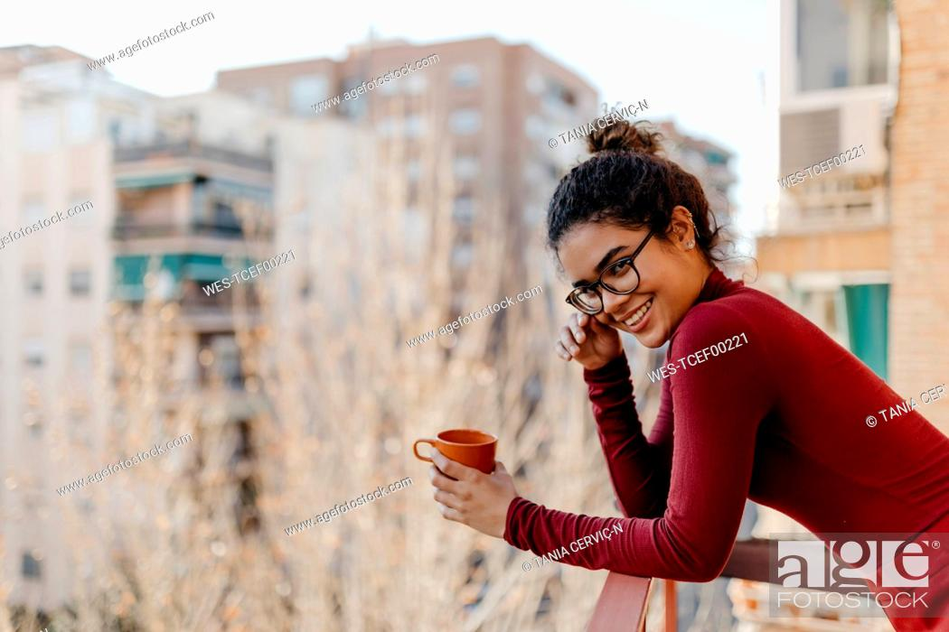 Stock Photo: Portrait of young woman wearing red turtleneck pullover, hand on glasses, standing with a cup on a balcony.