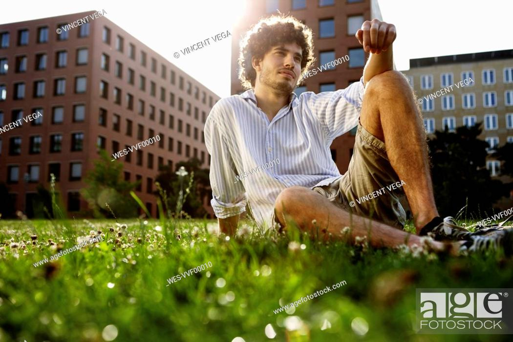 Stock Photo: Germany, Berlin, Young man relaxing on lawn, in background high rise buildings.