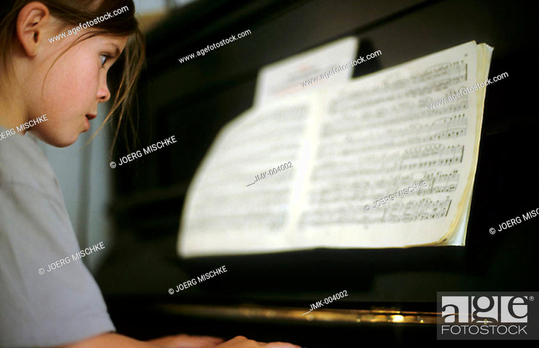 Photo de stock: A little girl, 5-10 years old, playing piano.
