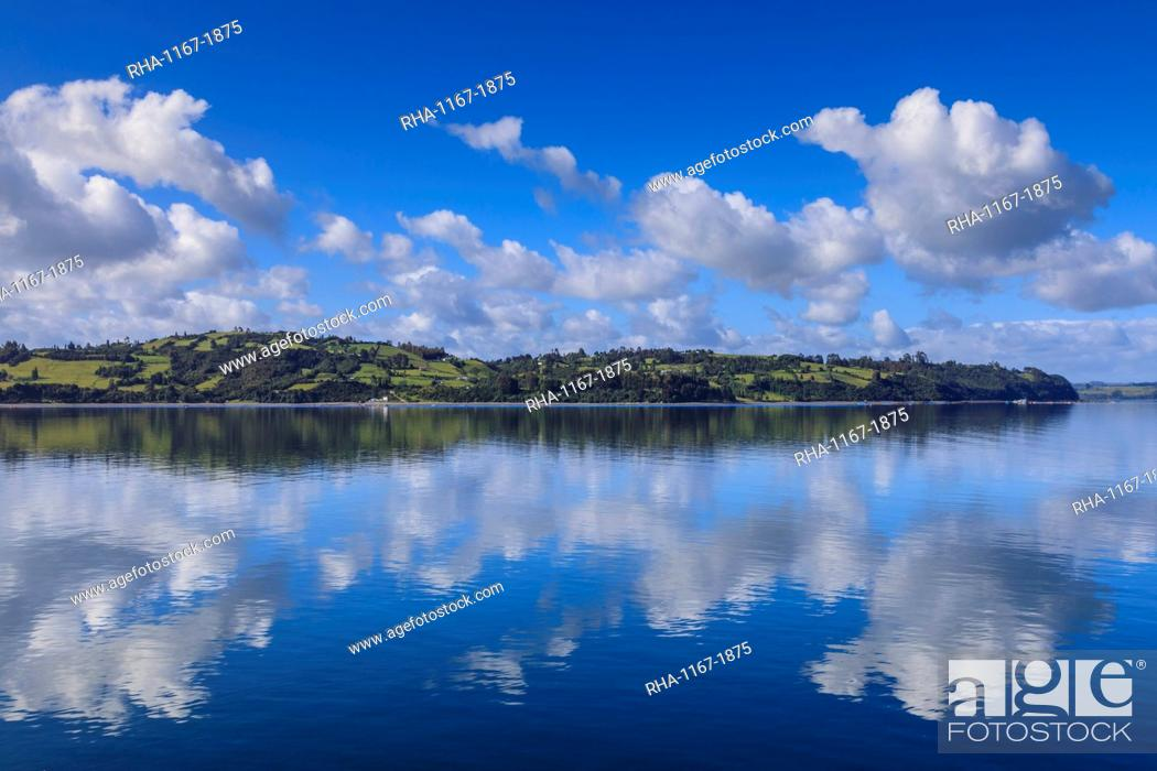 Stock Photo: Castro inlet reflections, rural scene, fluffy clouds and rolling hills, Isla Grande de Chiloe, Chilean Lake District, Chile, South America.